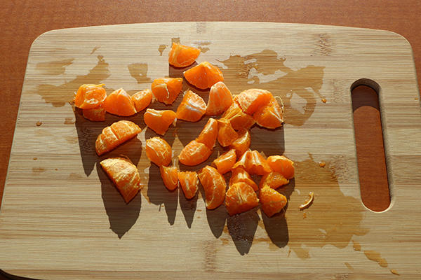 Making mandarin infused water. Be sure to chop the pieces in half!